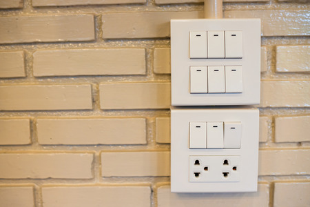 dimmer: Dimmer switch and light switch on switchboard.over  brick wall Stock Photo