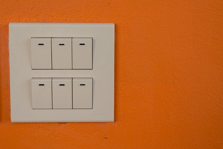 dimmer: Dimmer switch and light switch on switchboard.over wall