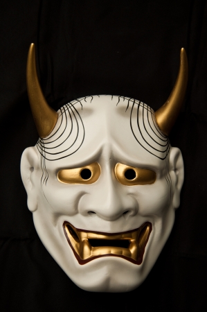 Japanese demon mask isolated on black background photo
