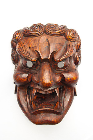 Japanese demon mask carving from wood isolated on white background photo