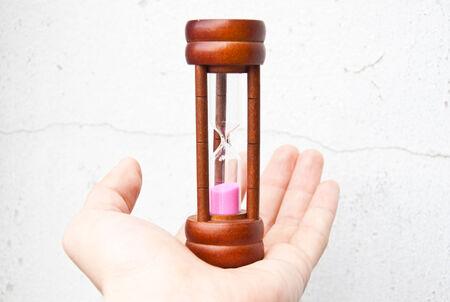 Hand holding hourglass photo