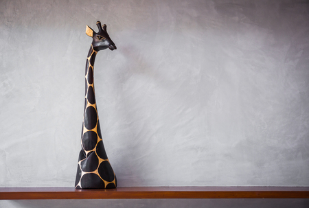 Wooden shelf with a giraffe statue. photo