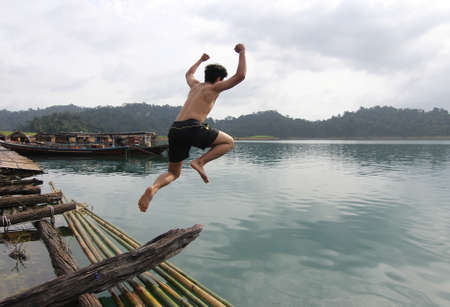 hobby hut: Motion blur shot of a young man jumping into water at thailand
