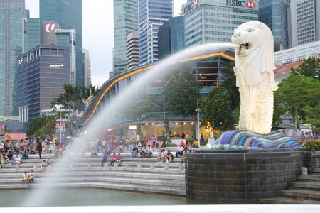 SINGAPORE - April11 ,2016: The Merlion fountain spouts water in front of the Singapore skyline on April 11, 2016 in Singapore. Merlion is a creature with a lion head, often seen as a symbol of Singapore Editorial