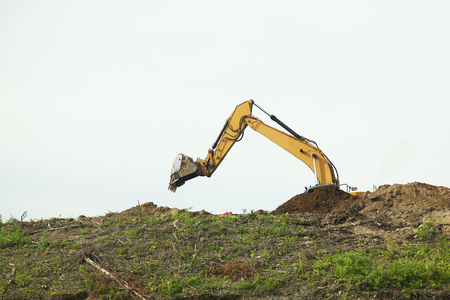 The backhoe was digging soil on top mountain.