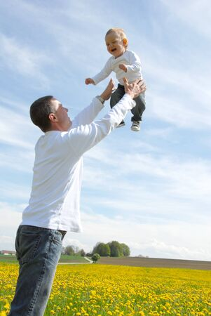 Father lifting his son up in the sky photo
