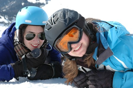 Portrait of two teenage girls laying in snow