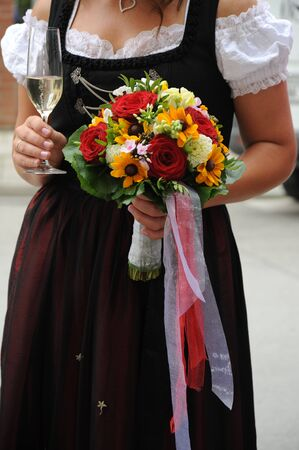 bride in dirndl with wedding flowers and a champagne photo