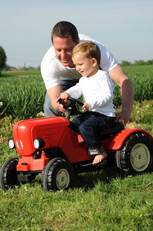 father and son with a red tractor photo