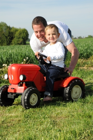 location shot: father and son with a red tractor