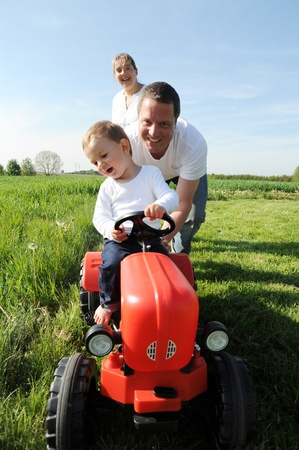 parents and young son with a red tractor photo