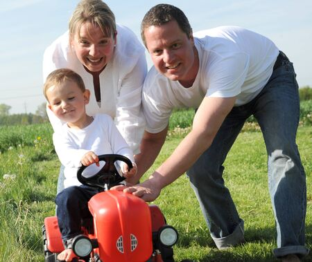 parents and young son with a red tractor