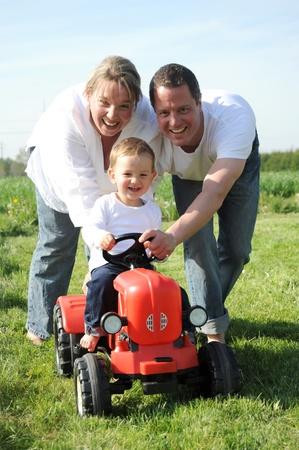 apoyo familiar: hijo de padres y j�venes con un tractor rojo