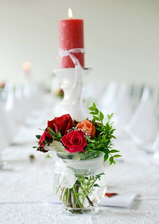 Bridal bouquet and candle on the wedding table