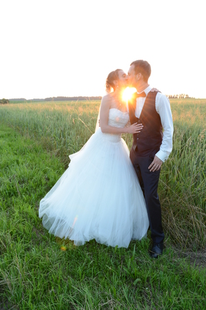 joyfully: bride and groom kissing at sunset