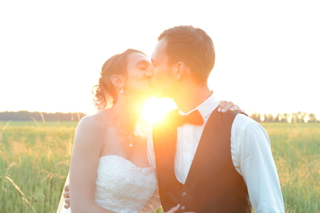 bride and groom kissing eachother at sunset Stock Photo