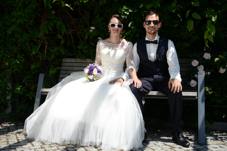 just married young couple sitting on a bench Stock Photo