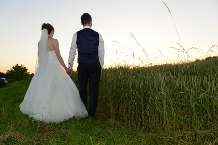 Bridal couple in sunset from behind