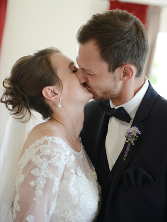 The bride and the bridegroom kissed after the wedding ceremony in the town hall Stock Photo