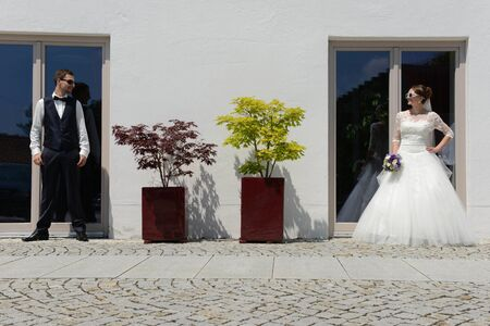 wedding couple in front of house looking to eachother