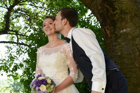 Happy married couple groom is kissing bride