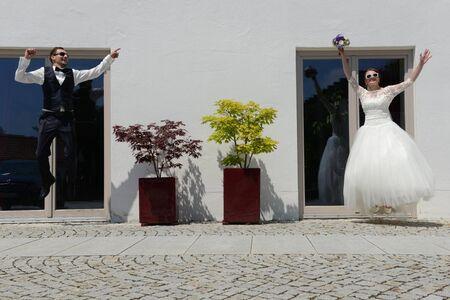 Joyful jumping fresh married couple Stock Photo