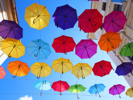 Colorful umbrellas hanging in a street in Timisoara Imagens