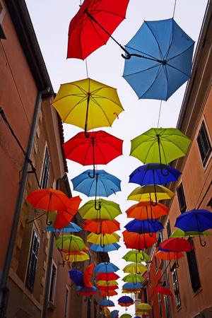 Colorful umbrellas hanging in a street in Novigrad, Croatia Imagens