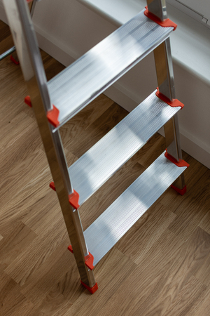 Top view on the iron stepladder, repairs in the house Standard-Bild