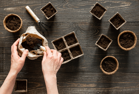 Woman pours ground in the eco friendly pots to plant seedlings,pots on wooden background, small bag with ground and garden trowel and rakes