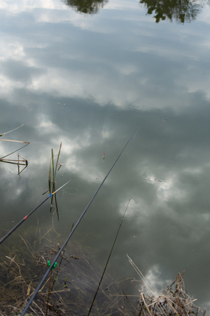 Reflection of clouds in the lake, fishing rod float in water, fishing Фото со стока