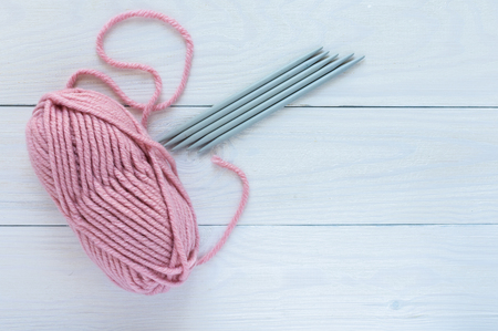 Pink skein with knitting needles isolated on white wooden background, knitting mittens or socks on 5 needles