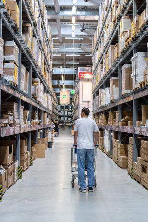 Berlin, Germany- May 24, 2019: Buyer man in store between row of shelves with goods, warehous in Ikea
