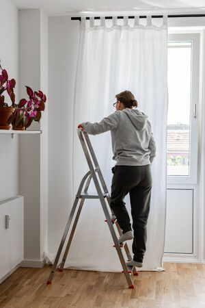 Woman stands on a stepladder near the window and hangs white curtains on the curtain rod Zdjęcie Seryjne