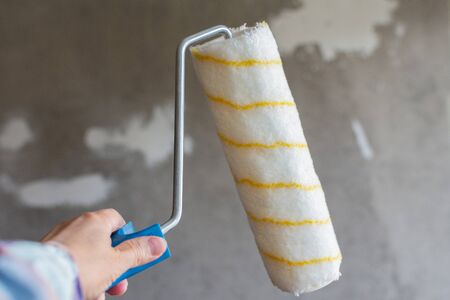A painter paints a concrete wall , a female hand with a paint roller for painting a wall Stockfoto