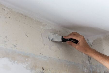 The worker covers the uneven walls, mans hands with a spatula and putty, apartment repair
