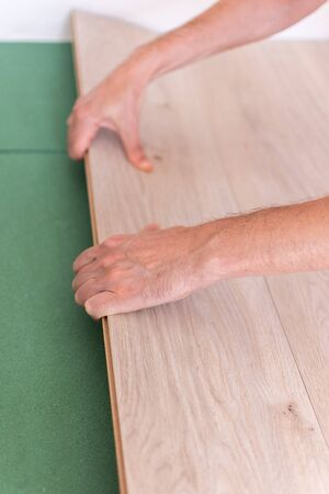 Installation laminate or parquet in the room, worker installing wooden laminate flooring, environmentally friendly soundproofing sheets
