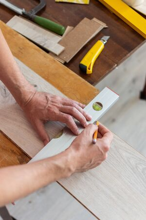 Installation laminate or parquet in the room, worker installing wooden laminate flooring, marking the length of the laminate