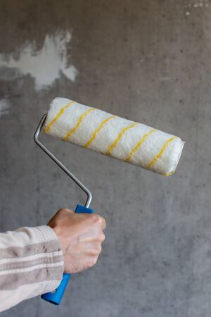 A painter paints a concrete wall , a male hand with a paint roller for painting a wall Stockfoto