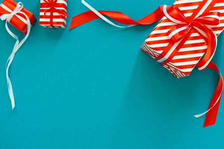 Festive background with gifts, gift box with ribbon and bow on a blue turquoise background, flat lay, top view Stockfoto