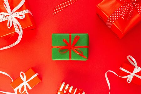 Festive background with colored gifts, gift boxes with ribbon and bow on red background, flat lay, top view Stockfoto
