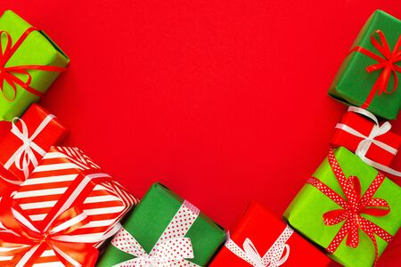 Festive background with colored gifts, gift boxes with ribbon and bow on red background, flat lay, top view, empty space for text Stockfoto