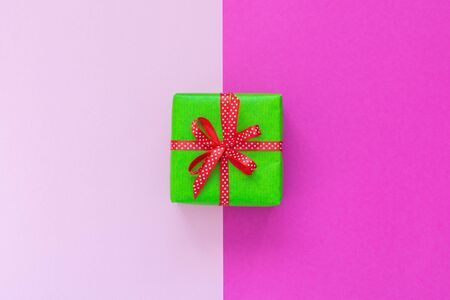 Festive background with gift, green gift box with ribbon in polka dots and bow on pink background, flat lay, top view