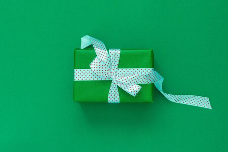 Festive background with gift, gift box with ribbon in polka dots and bow on green background, flat lay, top view