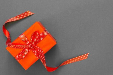 Festive background with gift, red gift box with ribbon in polka dots and bow on gray background, black friday concept, flat lay, top view