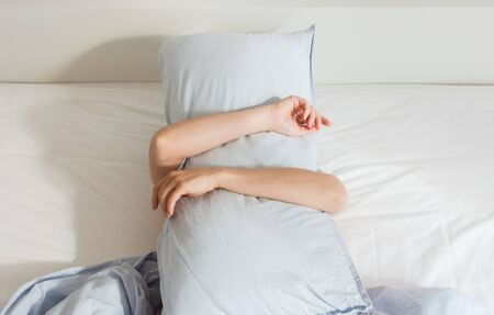 Part of the home or hotel interior, woman sleeping on a white bed with blue linens in the morning ,woman covered herself with a pillow