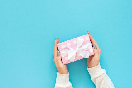 Girl holds gift box, pink gift box in polka dots with white ribbon and bow on a blue background , flat lay, top view, birthday or valentines day
