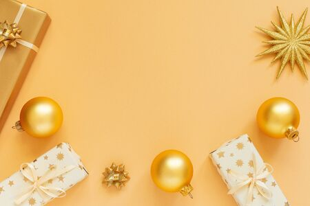 Festive background, gold background with glitter gold star and gift boxes and christmas balls, flat lay, top view, copy space