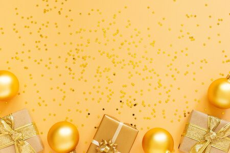 Festive background, gift boxes and christmas balls on background with glitter gold stars, flat lay, top view, copy space