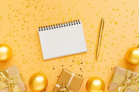 Holiday background, gold background with gift boxes and glitter gold christmas balls, open spiral notepad and pen, flat lay, top view, copy space